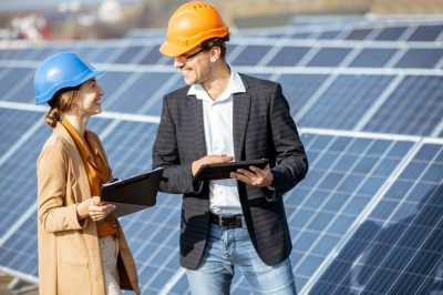 Man and woman dressed in the suits and hard hat as an engineers or business people examining solar station with digital tablet